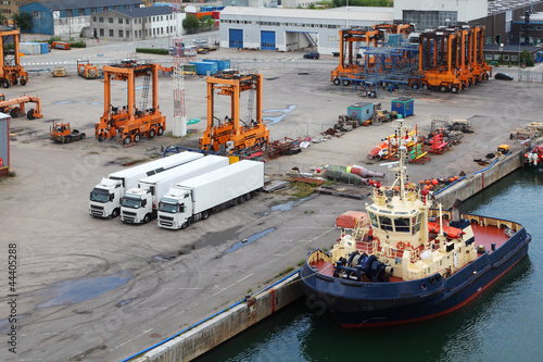 Photo  White lorries and orange loaders stand in port.