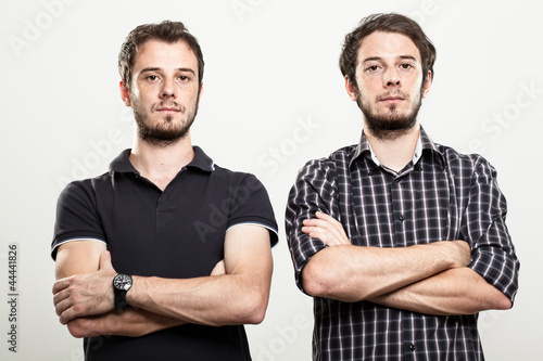 Photo  Two Serious Twins with Arms Folded