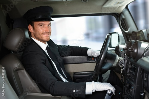 Photographie  Handsome chauffeur driving limousine smiling