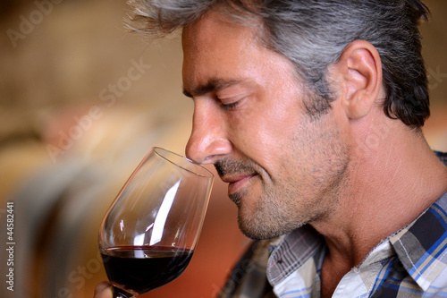 Fotografía  Closeup on winemaker smelling red wine in glass
