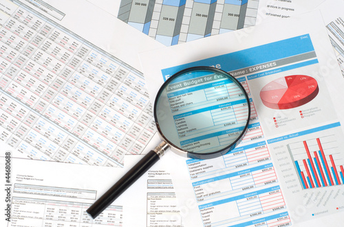 Photo  magnifying glass over financial reports