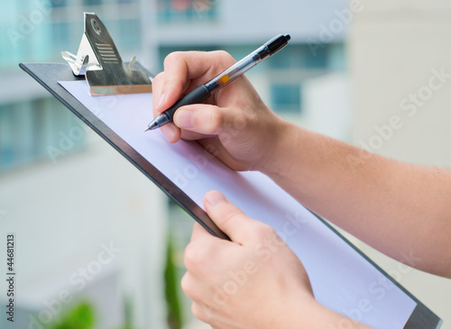 Foto Businessman Holding A Clipboard And Writing