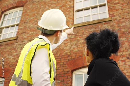 Fotografia  Surveyor or builder and homeowner looking at a property