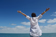 happy young woman with spreading arms to sky