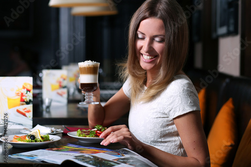 Foto op Canvas Kruidenierswinkel pretty young woman sitting in the cafe with a cup of coffee