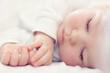 Leinwanddruck Bild - close-up portrait of a beautiful sleeping baby on white