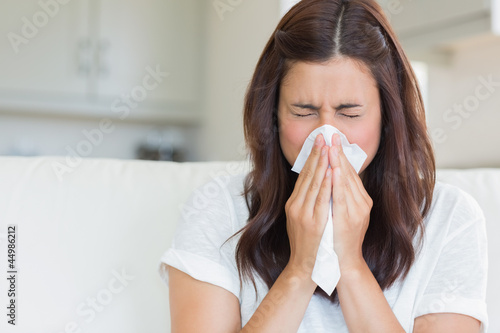 Photo  Brunette sneezing in a tissue