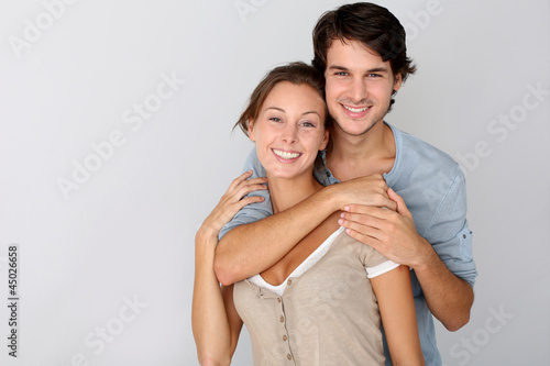 Fotografia  Cheerful young couple standing on white background, isolated