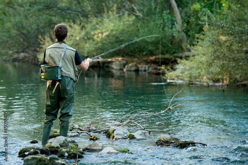 Obraz A fisherman fishing on a river - fototapety do salonu