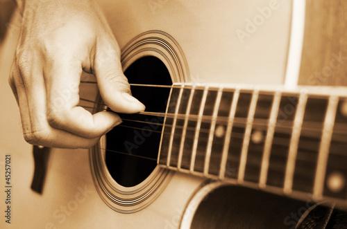 Fényképezés  Close up of guitarist hand playing acoustic guitar
