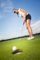 Fototapeta Golf Happy girl golfer putting ball into hole.