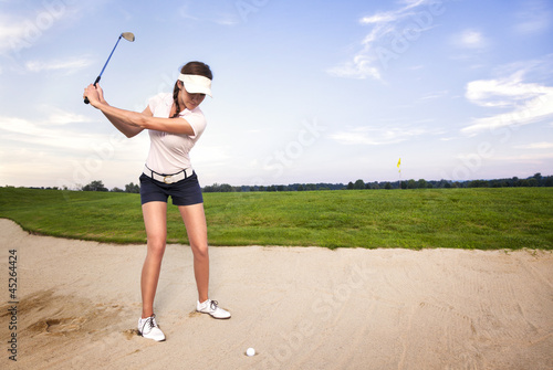 Deurstickers Golf Woman golf player in sand trap preparing to hit the ball.