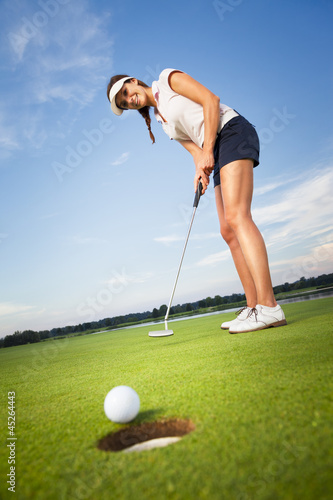 Happy girl golfer putting ball into hole. - 45264443