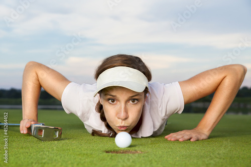 Valokuva  Girl golf player blowing ball into cup.