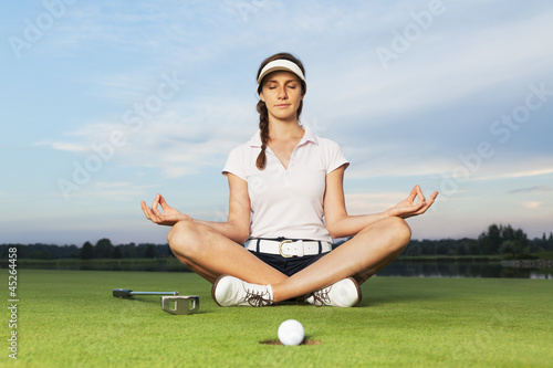 Deurstickers Golf Girl golfer sitting in yoga posture on golf course.