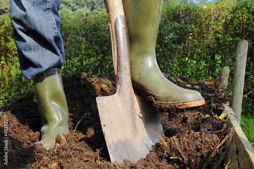 Fototapeta Mann beim Umgraben des Kompostes