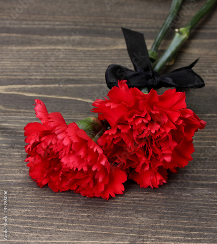 Papiers peints Rouge, noir, blanc carnations and black ribbon on grey wooden background