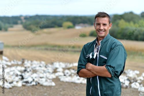 Fototapeta Duck breeder standing outside the farm