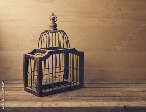 Fotografie, Obraz  Wooden empty bird cage on wooden table and background
