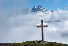 Wooden Cross In The Clouds In The Swiss Alps