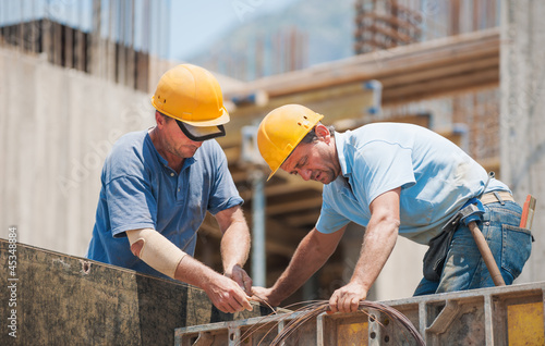 Fotografia  Construction workers working on cement formwork frames