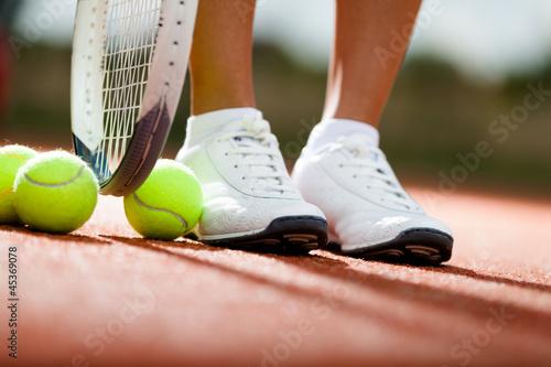 nogi-sportowca-w-poblizu-rakiety-tenisowej-i-pilki