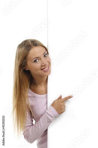 Plakát  Hübsche Frau zeigt seitlich leeres Plakat