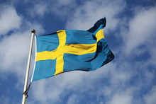 Waving Swedish Flag Against Blue Sky With Small White Clouds