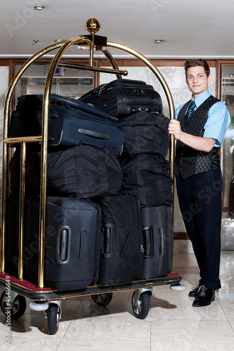 Fotomural Concierge with a pile of bags in luggage cart