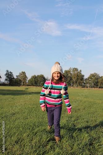a43160693c58c9 Fröhliches Mädchen im Herbst läuft über eine Wiese - Buy this stock ...