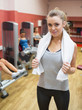 Woman with towel around neck in weights room