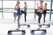 Four women raising their legs while doing aerobics