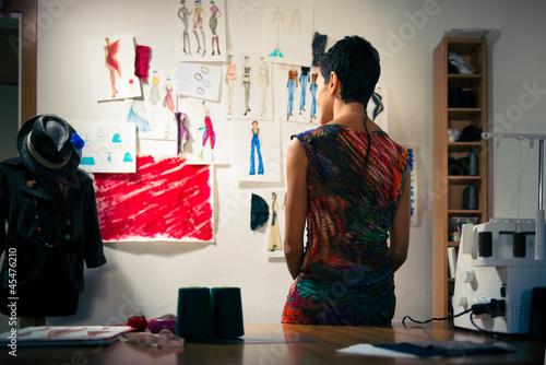 Fotografija  Female fashion designer contemplating drawings in studio