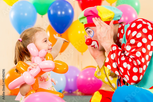 happy child girl and clown playing on birthday party Fototapete