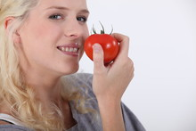 Young Woman Eating A Tomato