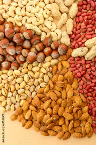 assortment of tasty nuts, on beige background