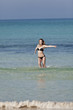 Frau mit Bikini im meer beim Springen Hochformat