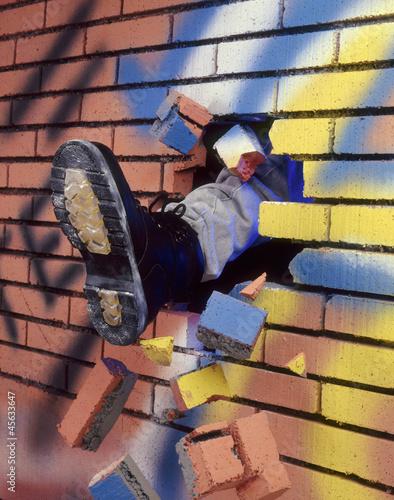 Valokuvatapetti Pateando y rompiendo un muro de ladrillos.