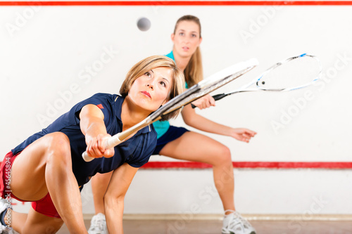 Squash sport - women playing on gym court