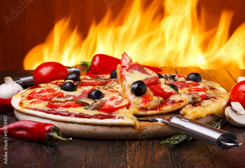 Foto op Plexiglas Pizzeria Hot pizza with oven fire on background