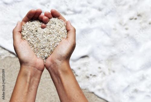 Foto-Leinwand - Mellow heart shaping female hands above beach