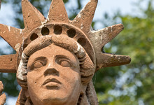 Face And Head Of A Terracotta Liberty Statue In A Garden.