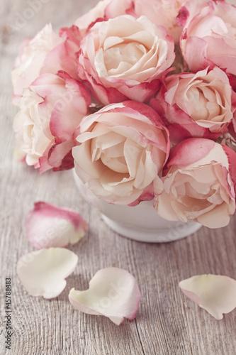 Obraz Pastelowe róże w wazonie na drewnianym stole - fototapety do salonu