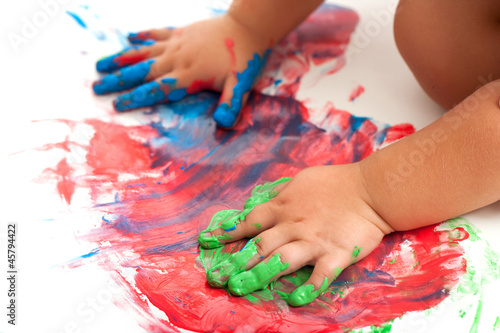 Babies hands painting colorful mosaic.