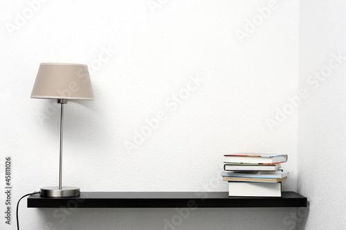 Fotografía  Estantería en la pared con lámpara y libros