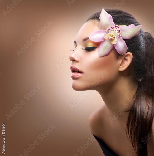 stylowa-dziewczyna-z-kwiatem-orchidei-we-wlosach-na-czekoladowym-tle
