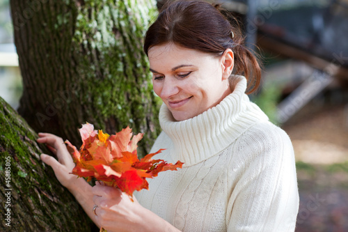 Spoed Foto op Canvas Canada Beautiful girl in the autumn park collects leaves