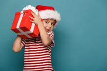 Funny Child In Santa Red Hat Holding Christmas Gift In Hand.