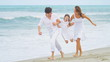 Caucasian parents daughter dressed in white enjoying beach vacation together