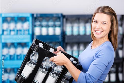 Fotografiet  frau kauft eine kiste sprudel